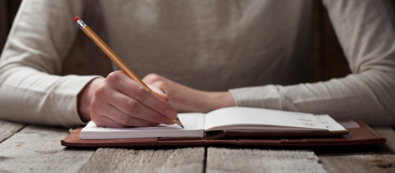 Hand writing with a pen in a notebook